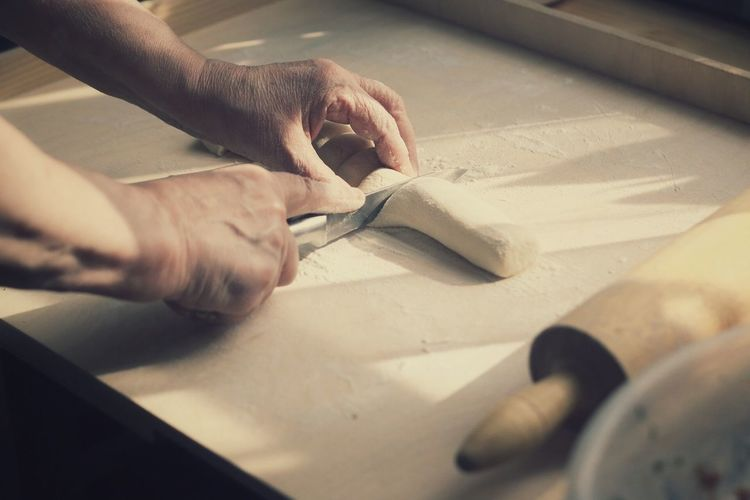 Close-Up Of Cropped Hand Cutting Dough