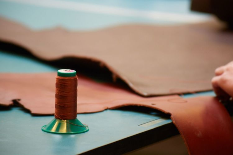 Close-up of spool and leather on table in workshop