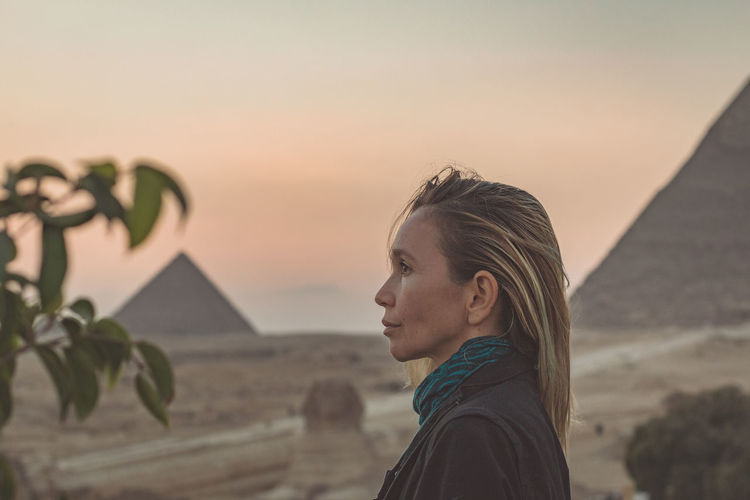 Woman looking away against pyramids and sky