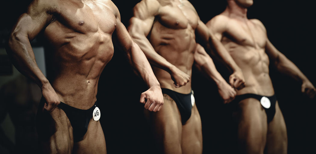 Body builders flexing muscles while posing on stage