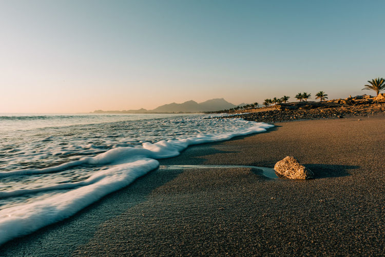 Scenic view of beach against clear sky during sunrise