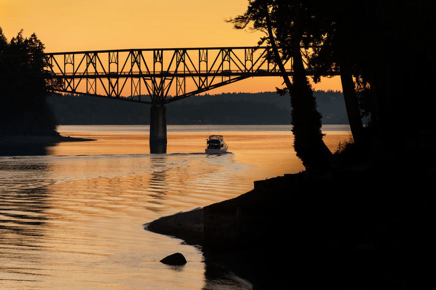 Agate Pass Bridge. A boat passes under the Agate Pass bridge during a lovely sunset on New Years Eve. Agate Pass is a high-current tidal strait in Puget Sound connecting Port Madison and mainland Kitsap County. It lies between Bainbridge Island and the mainland of the Kitsap Peninsula near Suquamish. Agate Pass Boat Boating Bridge Bridge - Man Made Structure Built Structure Colorful Dusk Engineering Getting Away From It All Kitsap County Light Olympic Peninsula Orange Outdoors Pacific Northwest  Power Boats Puget Sound Sea Silhouette Sunset Wakeup Washington Water Waterfront