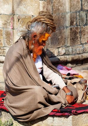 A 'professional sadhu', a fake ascetic who makes a living having his photo taken, makes a call on his mobile (admittedly, a frugal-looking model) at Pashupatinath temple, Nepal. Note also the wristwatch and the packed lunch! Hinduism Kathmandu Nepal Pashupatinath Sadhu Ascetic Ascetism Fake Outdoors Professional Worldly