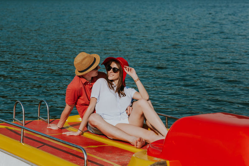 Cheerful man and woman cuddling while boating. Portrait of couple in love sharing tender moments on pedal boat on warm sunny day. Boating Couple Holiday Hot Day Love Summertime Vacations Young Boat Boyfriend Caucasian Feet Girlfriend Lake Outdoors Pedalo Relax Resting River Sea Summer Sunglasses Sunhat Two People Water