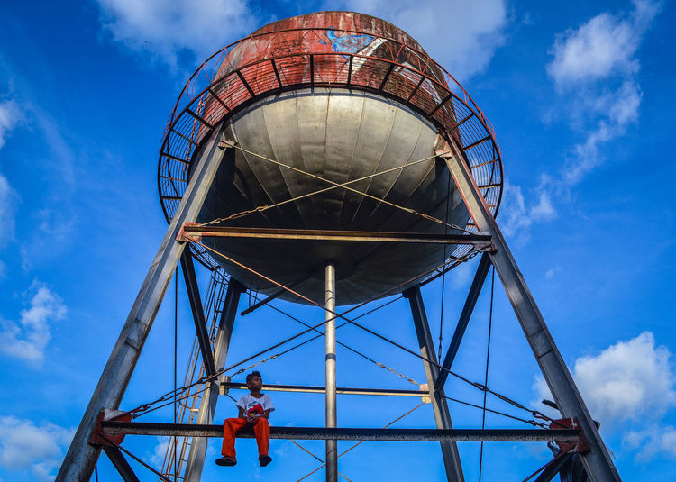 Low angle view of man sitting on water tower against blue sky