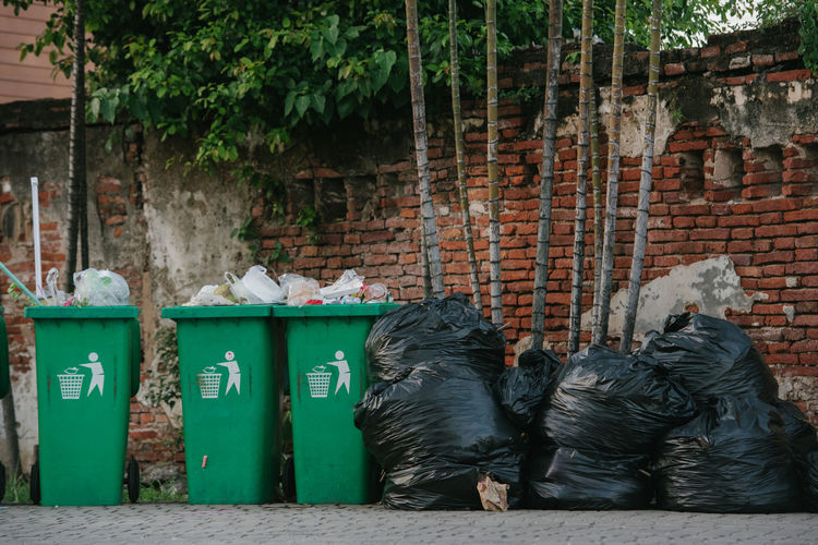 Rubbish green bin on the walkway and garbage bags dirty on the ground. Rubbish Bin Walkway Garbage Bags Black Bag City Clean Dirt Dirty Discarded Disposal Dumpling  Dusbin Ecology Environment Garbage Garden Household Equipment Junk Park Plastic Pollution Recycle Refuse