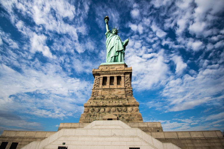 Statue of Liberty high in the Sky - Architecture Art Art And Craft Clouds Column Composition Creativity Famous Place History Human Representation Low Angle View Monument NYC Perspective Sculpture Sky Statue Statue Of Liberty Blue Wave Travel The Architect - 2018 EyeEm Awards The Traveler - 2018 EyeEm Awards
