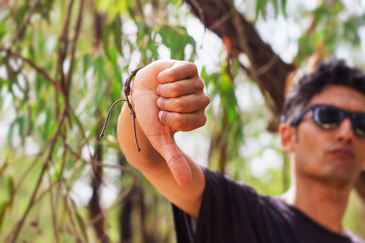 Close-up of young man gesturing outdoors