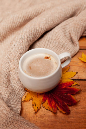 Coffee with milk foam in a white mug, autumn red and yellow maple leaves and a knitted beige sweater