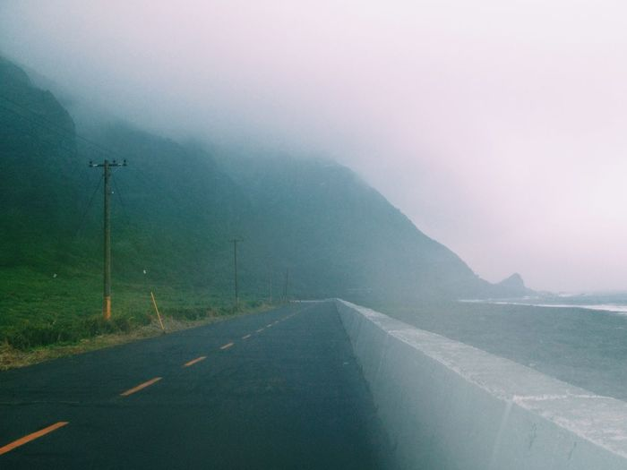 Coastal road against mountain in foggy weather