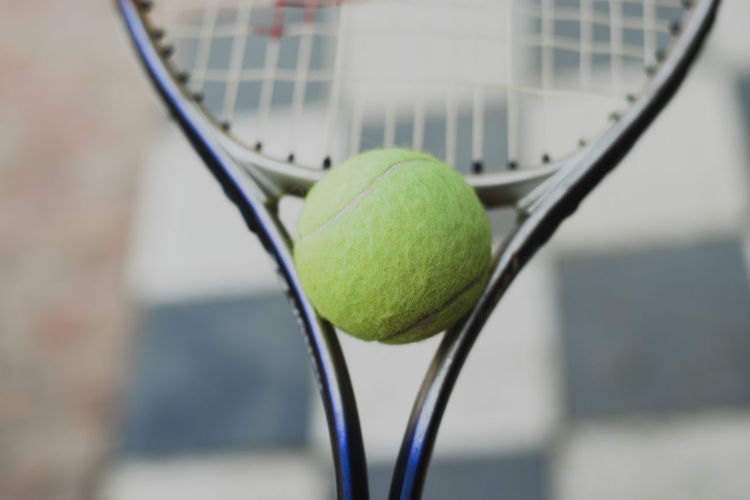 Close-up of tennis ball on tennis racket