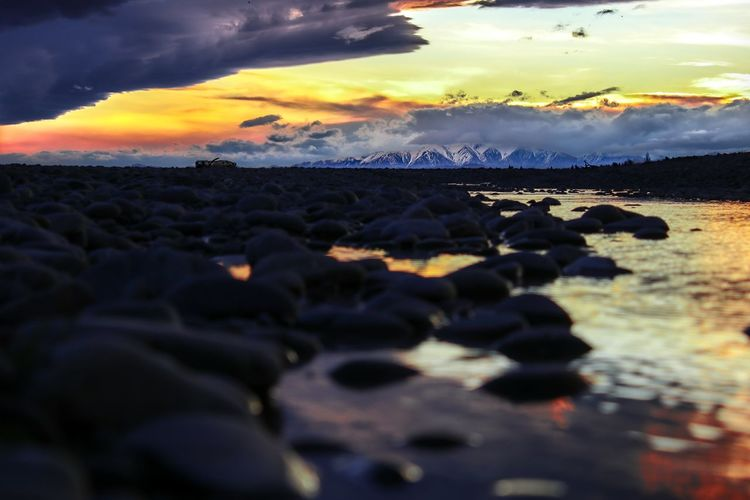 Surface level of rocks on beach against sky during sunset