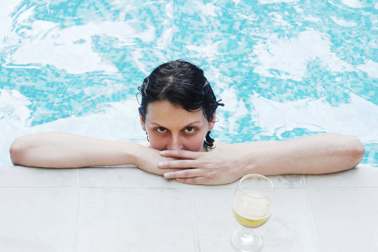 Portrait of woman in swimming pool by drink