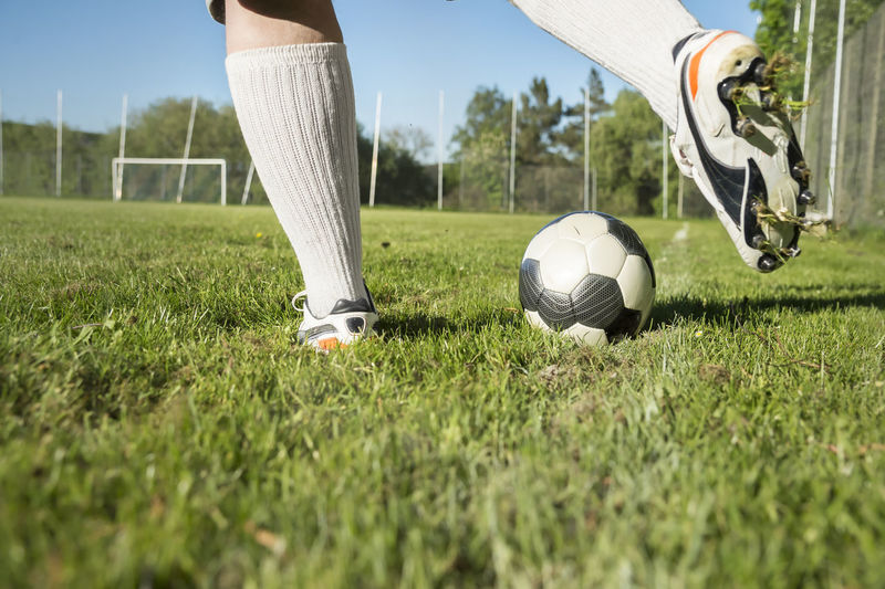 Low section of person playing soccer on grassy field