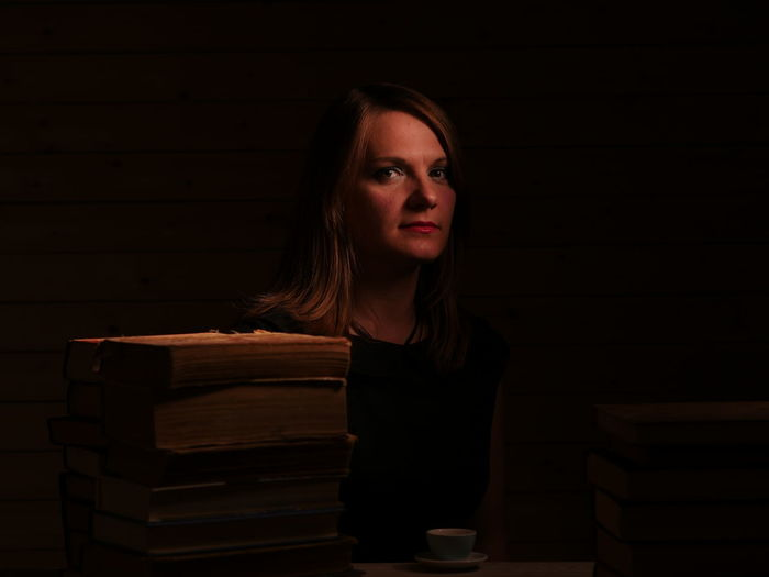 Portrait of young woman sitting on stack of books