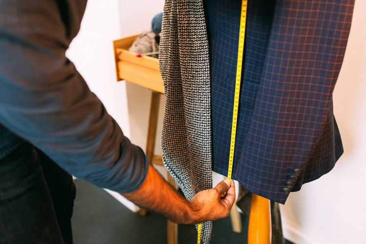 Midsection of man measuring clothing in store