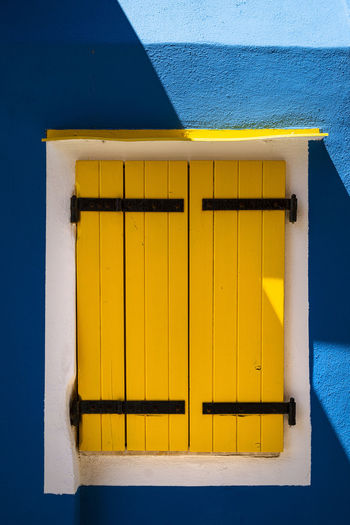Low angle view of yellow house against blue sky