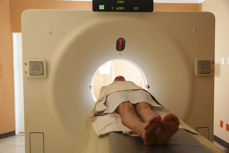 Patient lying at entrance of cat scan machine in medical examination room