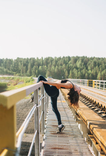Full length of woman exercising on railway bridge against sky