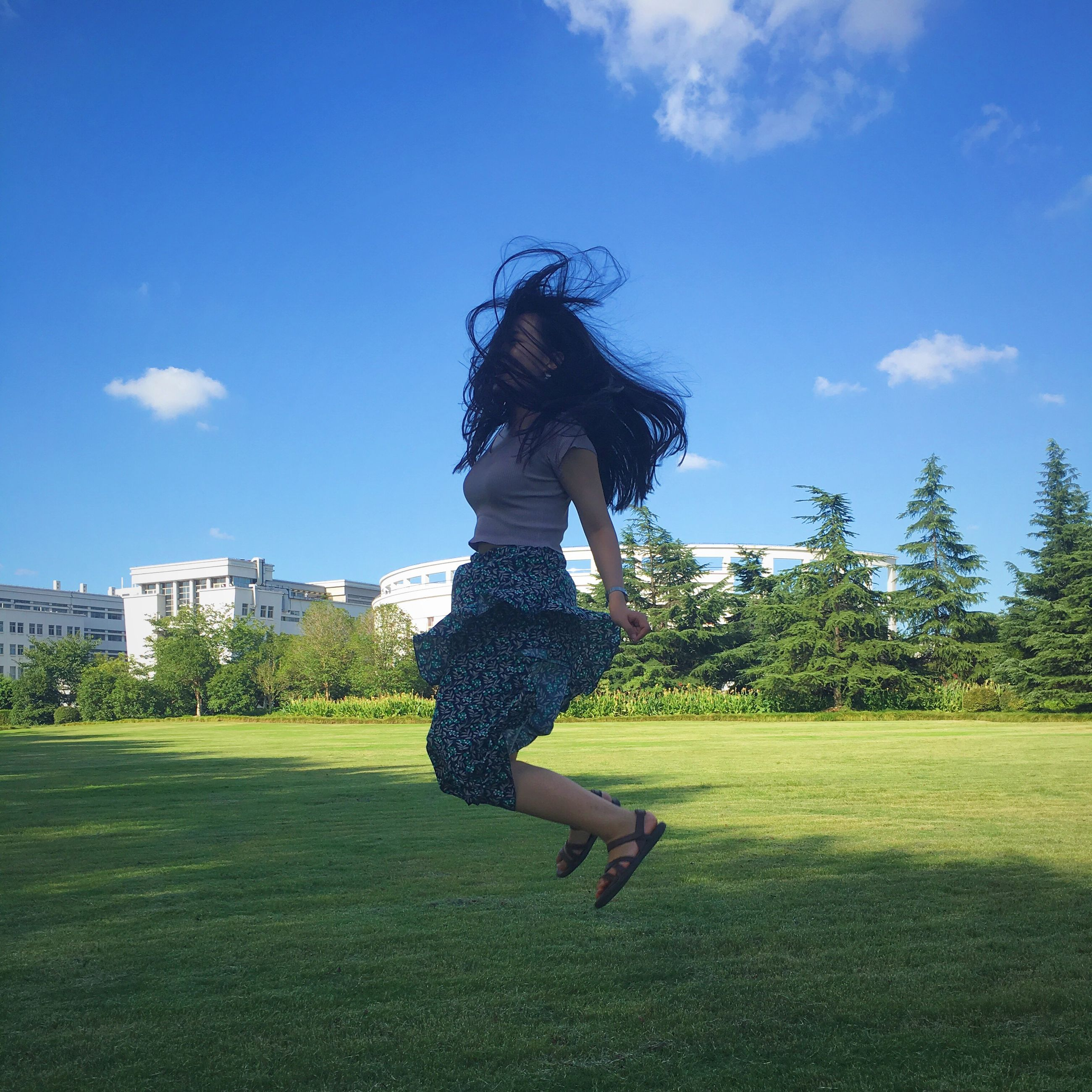 REAR VIEW OF GIRL JUMPING ON GRASSY FIELD