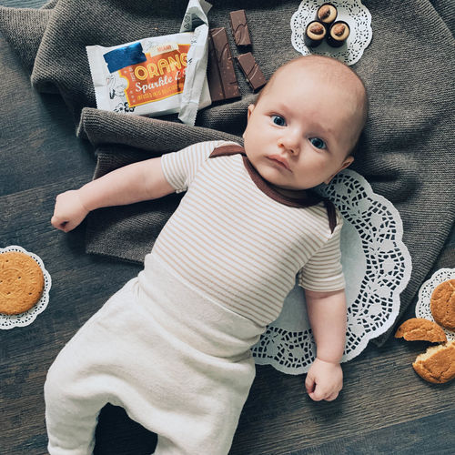 Baby Young Child Real People Childhood Babyhood High Angle View Toddler  Innocence One Person Home Interior Indoors  Cute Casual Clothing Leisure Activity Lifestyles Front View Looking At Camera Baby Boy Sweets Baby And Sweets Brown Colour