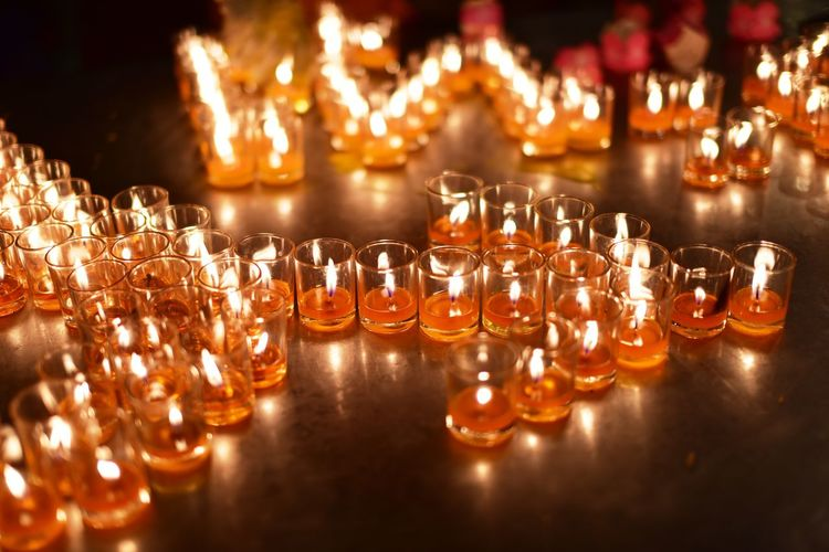 Illuminated candles on glass table