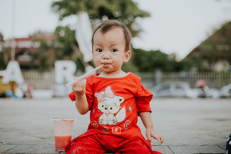 Portrait of cute girl drinking juice at park