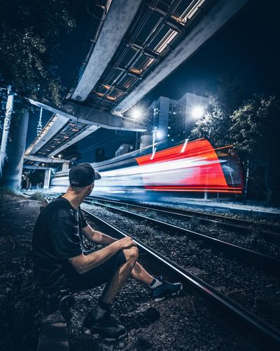 Young man sitting by railroad track at night