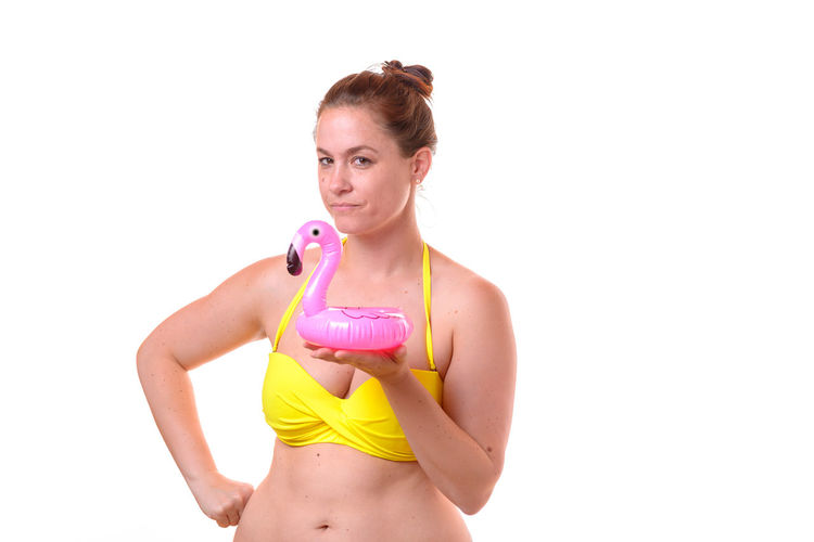 Portrait Of Mid Adult Woman In Bikini Holding Inflatable Ring While Standing Against White Background
