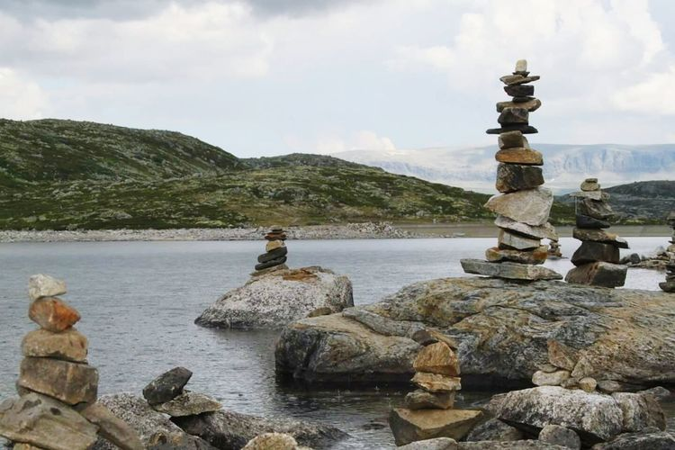 Stack of stones on rock by river against sky