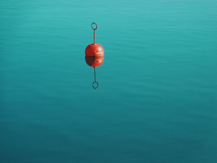 Red buoy floating on water