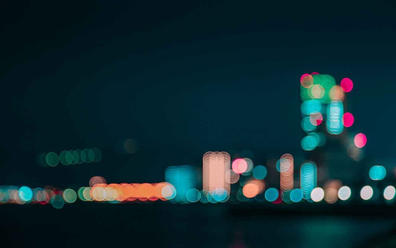 Defocused Image Of Illuminated Lights In City Against Sky At Night