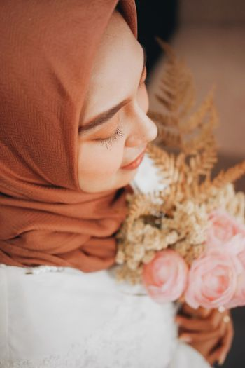 Close-up of woman in hijab holding flowering bouquet