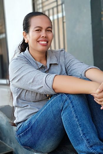 Portrait of smiling woman sitting outdoors