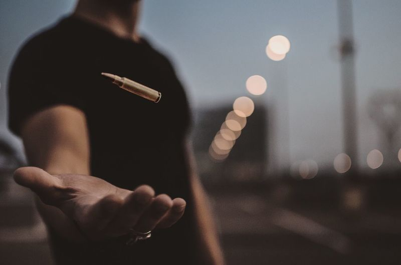 Midsection Of Man Levitating Bullet At Dusk