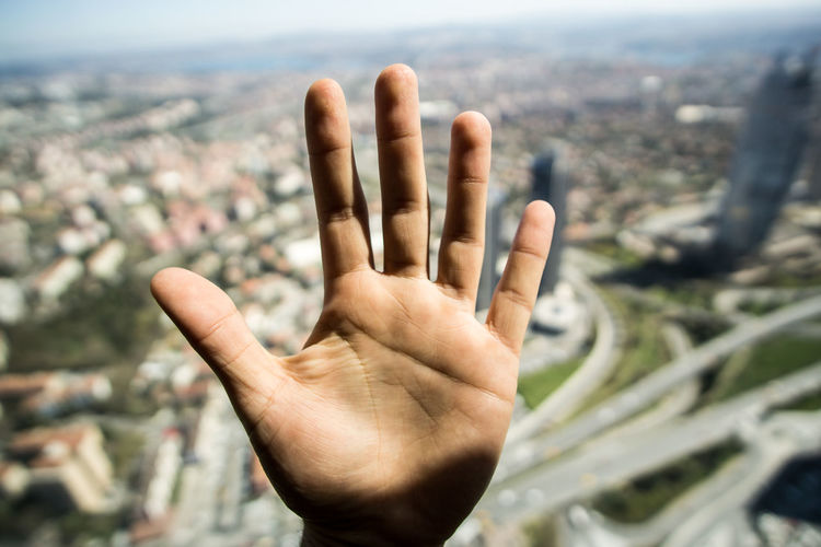 Close-up of human hand against cityscape
