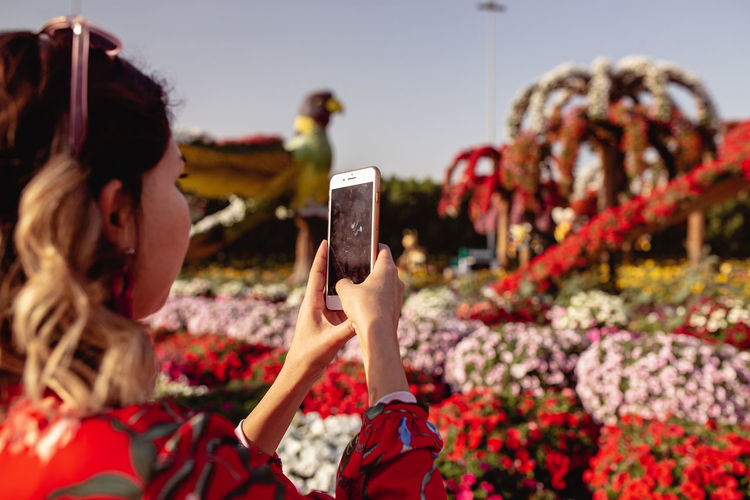 Close-up of young woman taking picture on mobile phone in ornamental garden