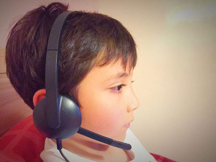 A young boy wearing a computer headset. Brown Hair Concentrating Concentration Young Boy Child Microphone Headset Headshot Portrait Childhood Child One Person Real People Close-up Indoors  Leisure Activity Headphones Boys Innocence