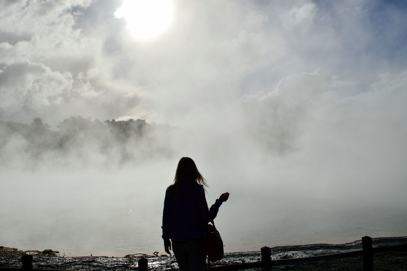 Silhouette of woman standing on landscape against cloudy sky