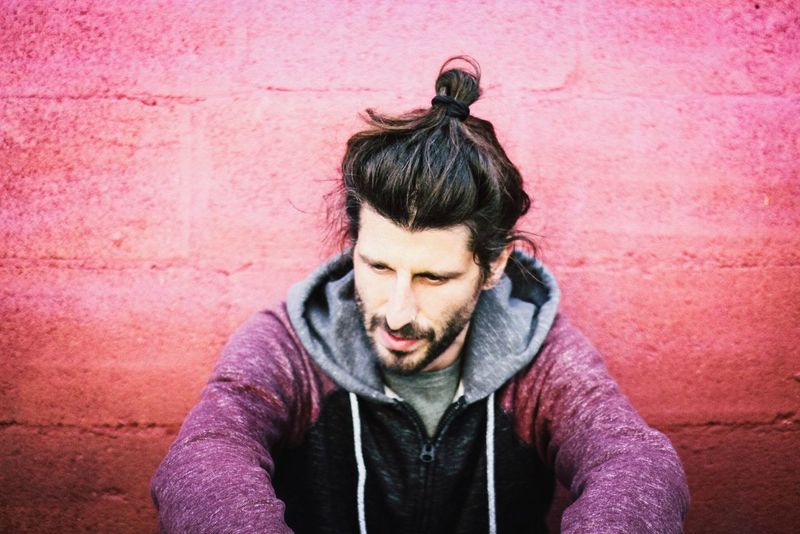 young man with long hair and stylish beard Male Model Sweater Manbun Pink Wall Pink Color One Person Real People Outdoors Hooded Shirt Day Young Adult Beard Lifestyles Only Men Adult One Man Only Adults Only