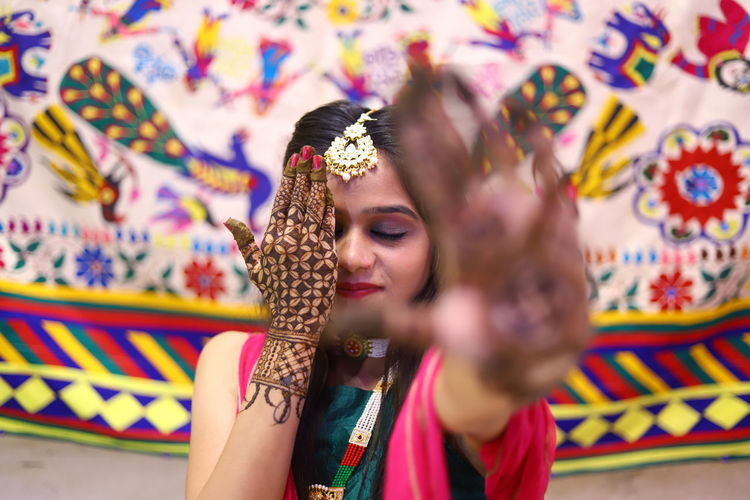 Close-up of bride with henna tattoo hiding face with hand