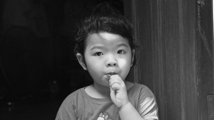Portrait of cute girl sucking candy