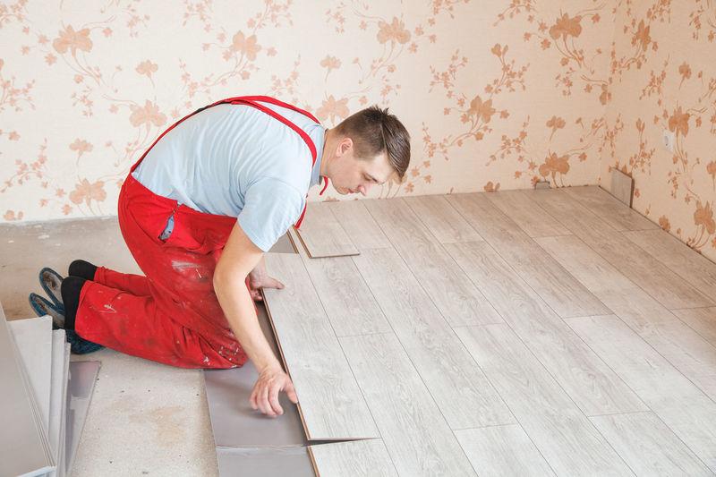 Man Putting Hardwood Floor Panels In Home