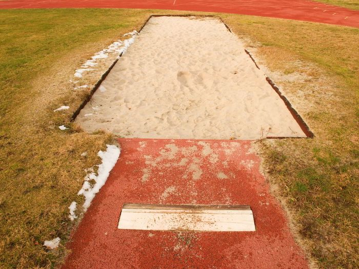 Lane for the long jump. sandy red retrack, white ake-off board. poor grass around.