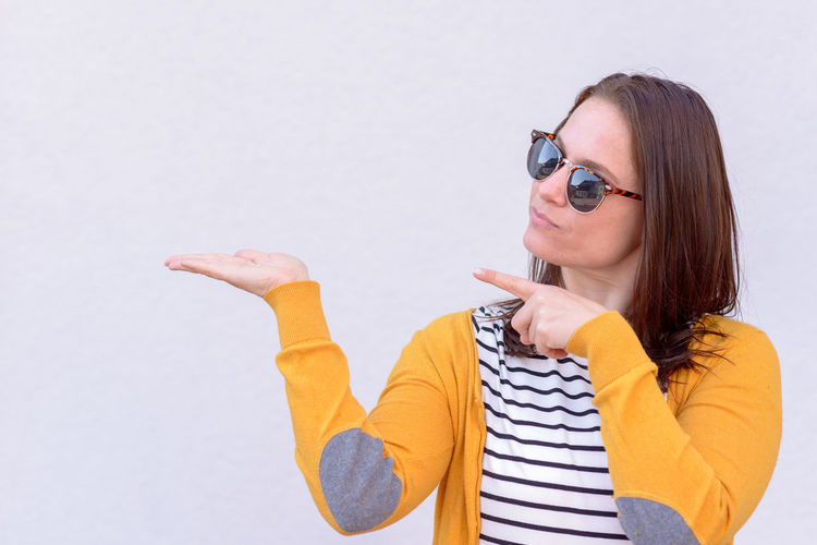 Portrait of mid adult woman in sunglasses gesturing while standing against white background