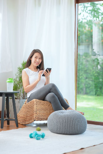 Young woman using phone while sitting on laptop