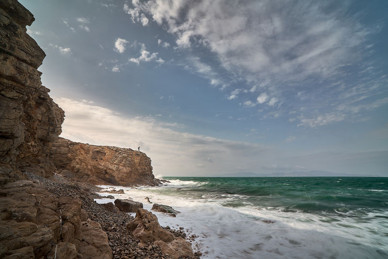 Man walks by cliff with storm Sea Water Sky Scenics - Nature Beauty In Nature Beach Land Cloud - Sky Rock Horizon Over Water Horizon Solid Rock - Object Nature Tranquility Tranquil Scene Motion Rock Formation Wave No People Outdoors