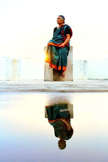 Reflection of woman in puddle against clear sky during sunset