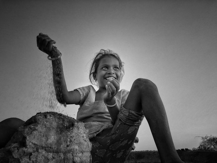 Smiling girl looking away while putting sand on rock against clear sky