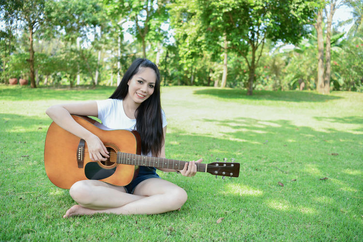 Portrait of smiling young woman playing guitar while sitting on grass at park